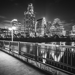 Austin skyline at night black and white picture with a bridge railing along the colorado river. Austin is a major city in the Southwestern United States of America. Photo was taken in 2016. © Paul Velgos with All Rights Reserved.