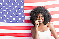 Portrait of young woman with fizzy hairstyle standing against American flag