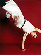 Young man doing a one arm handstand.