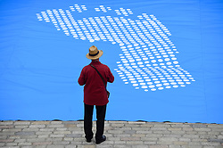 © Licensed to London News Pictures. 24/06/2019. LONDON, UK.  A man takes part in an opening event at Somersert House for Fly The Flag, a major new project marking the 70th anniversary of the Universal Declaration of Human Rights for which artist and activist Ai Weiwei has designed a new flag.  Photo credit: Stephen Chung/LNP