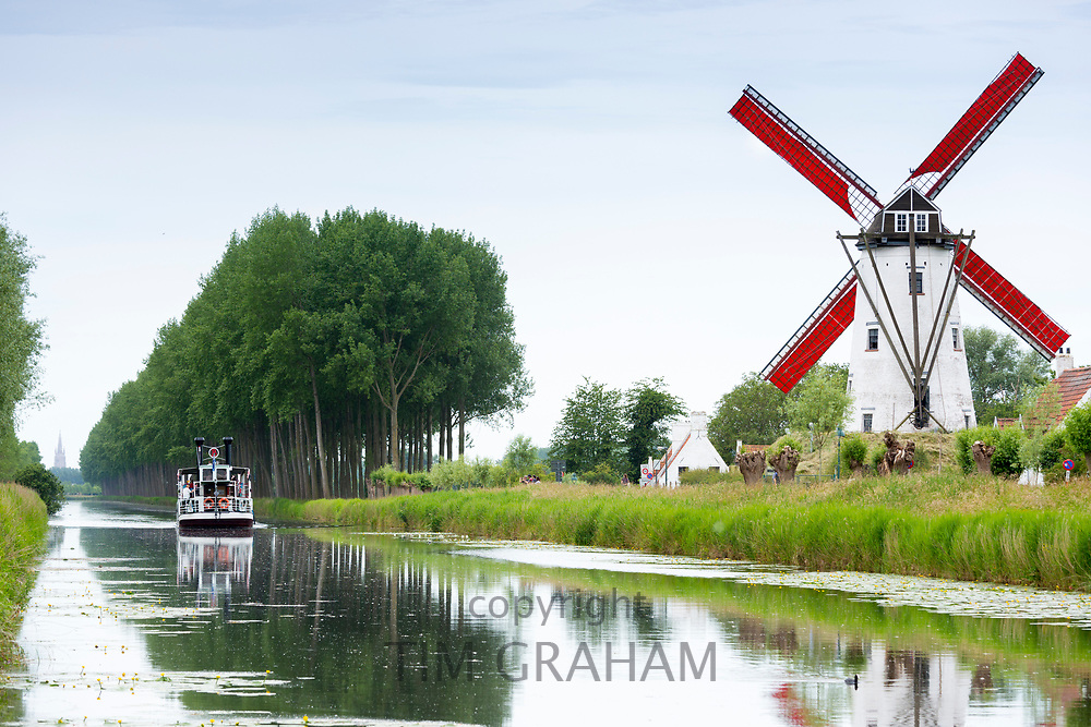 Tourist paddle steamer passes Schellemolen windmill on Damse Vaart Canal at Damme, West Flanders, Belgium