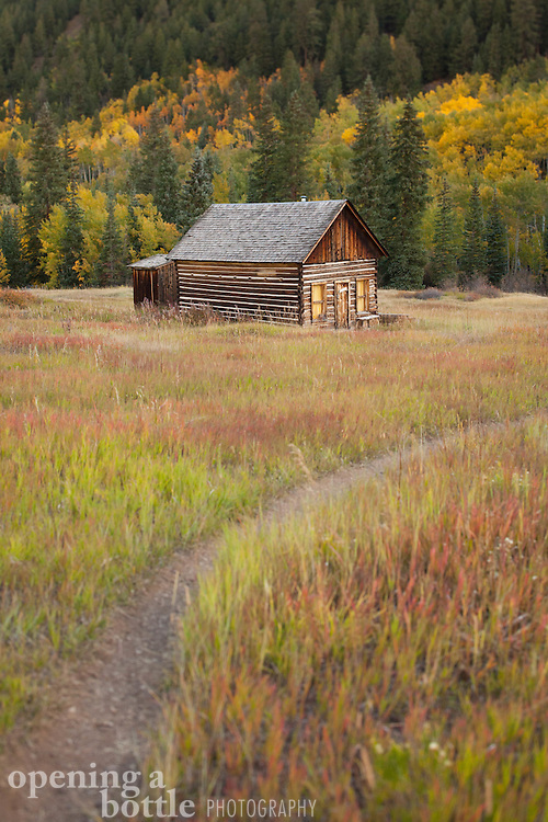 A lone cabin and path in a ghost town with fall color and aspen trees in the distance, Ashcroft, near Aspen, Colorado.