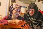 Novice nun, Maria, shows a webpage on her smartphone to octogenarian nun, Christina, at the Serbian Orthodox St. John of Kronstadt monastery, near the village of Korita, Republika Srpska, Bosnia and Herzegovina.