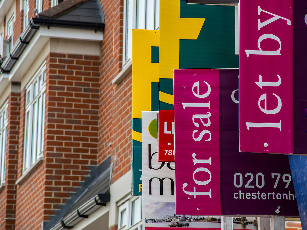 Competition in the housing market. A huge bunch of estate agents for sale and rental signs appear to be on one property in a street near Clapham Junction, London, UK, 07 August 2013.