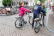 In Utrecht kijken twee oudere fietsers met hun elektrische fiets in de hand rond in de binnenstad.<br /> <br /> In Utrecht two older cyclists with their electric bike in hand watch around in the city.