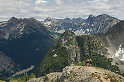 Hikers admoring view from summit of Maple Pass Trail, North Cascades Washington