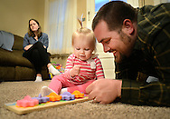 SELLERSVILLE, PA -  MARCH 7:  Emma Davies (C), 1 year old, plays in the living room with her father Jeremy Davies (R) as her mother Lisa Davies (L) watches March 7, 2014 in Sellersville, Pennsylvania. Emma Davies is suffering from a rare hematological disease. She will be getting a bone marrow transplant from her older sister. With bills stacking up, a friend of the Davies family has set up an online fundraiser to help.(Photo by William Thomas Cain/Cain Images)