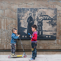 Shanghai, China - April 7, 2013: two young chinese children discussing in front of a communist historic poster at the city of Shanghai in China on april 7th, 2013