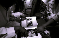 Khost, 19 August 2005..Afghans sitting on the dinning table, wearing long tunic over baggy trousers, look at a photographic book