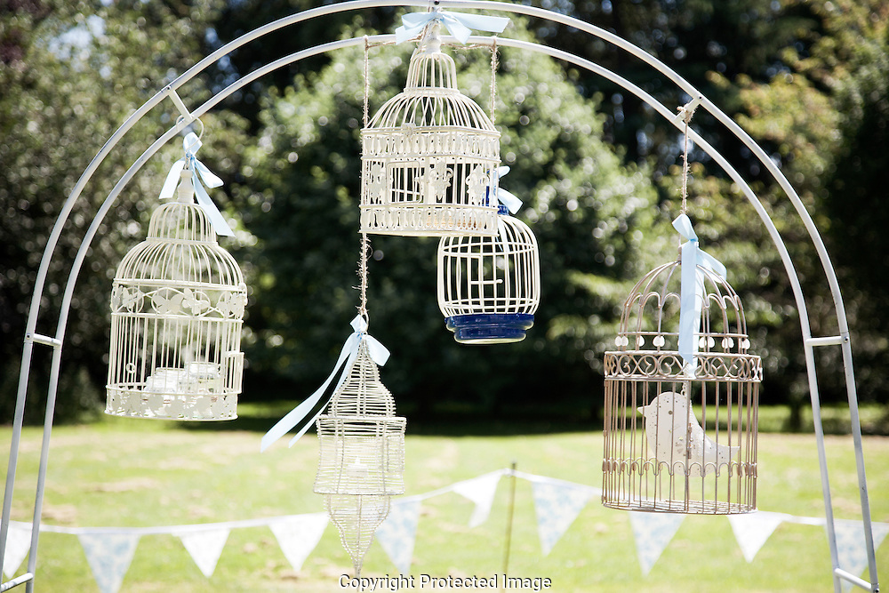 White bird cages tied with ribbons hang from arch in garden decorated with bunting for wedding reception vintage shabby chic