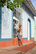 A man and woman talking through bars on a window and colourfully painted<br /> colonial buildings in Trinidad, Cuba