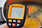 Handheld laser remote thermometer measures the temperature of boiling oil 146 degrees Celsius
