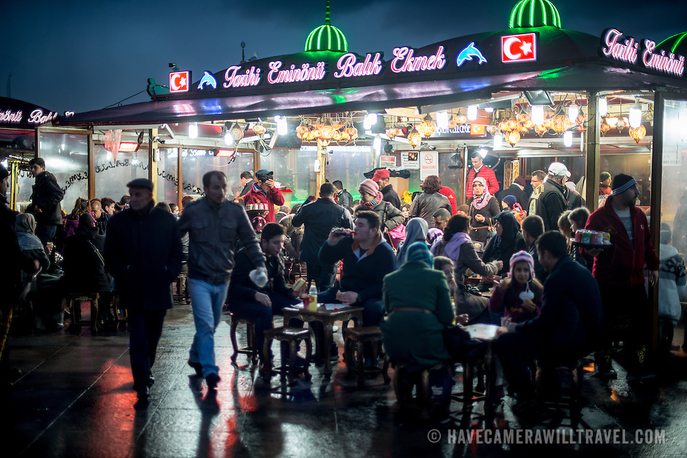 Diners eat fish sandwiches on the bustling waterfront of the Eminonu district of Istanbul.