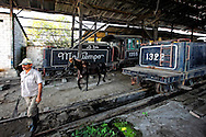 A man leads his horse past old steam trains in Cruces, Cuba. These are relics of the Cuban sugar industry.