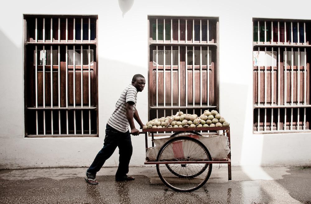 A man pushes a  cart of oranges through Stonetown, Zanzibar