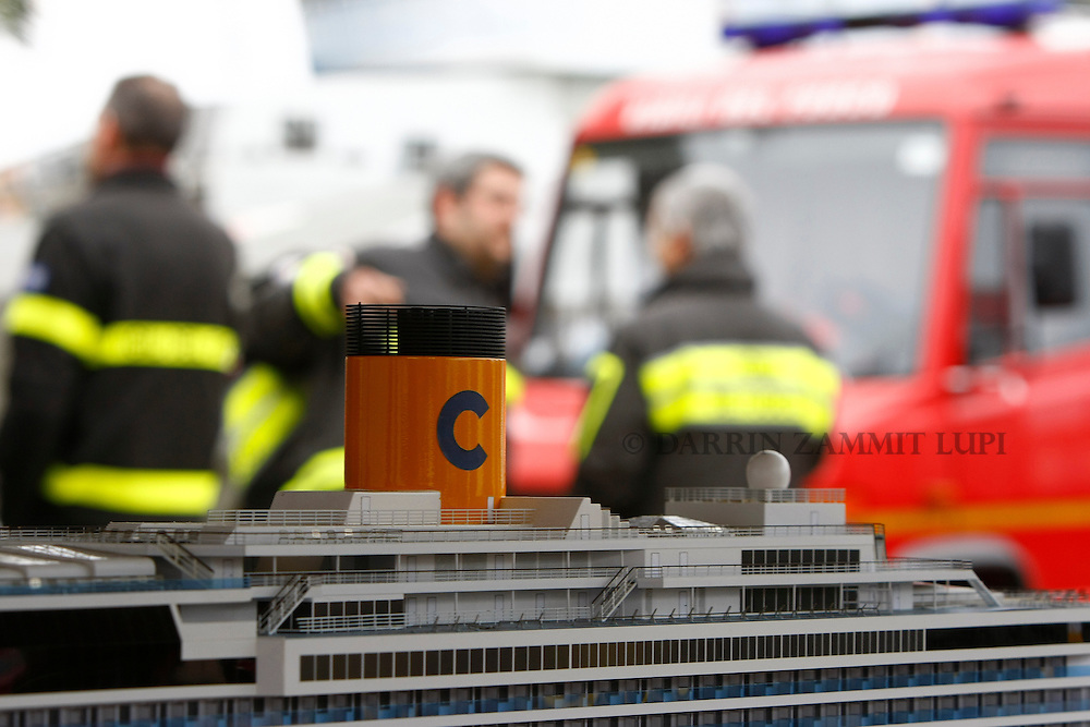 Firefighters talk near a model of the cruise ship Costa Serena, sister ship to the cruise liner Costa Concordia, at their operations centre at Giglio island January 31, 2012. Italian authorities have ended the search for bodies on the submerged sections of the capsized Costa Concordia, more than two weeks after the giant cruise liner capsized off the Tuscan coast, officials said on Tuesday...REUTERS/Darrin Zammit Lupi (ITALY)