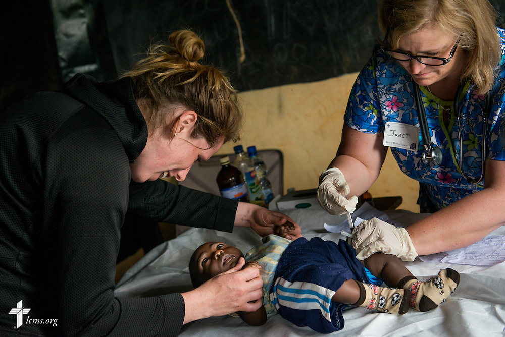 Nurses Casey Peters (left) of  Dover, N.H, and Janet Brown of Martinsville., Ind., treat an infant during the Mercy Medical Team clinic Wednesday, June 11, 2014, at the Luanda Doho Primary School in Kakmega County, Kenya. LCMS Communications/Erik M. Lunsford