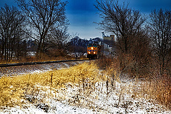Union Pacific Engine 6015  a GE AC44CWCTE, pulls a line of flats carrying containers and trailers through a snow covered railbed along old Rt. 66 south of Shirley Illinois past the crossing at county road E750N.
