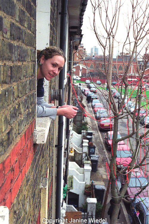 Woman looking out the window at Saint agnes Place squat at the Oval Kennington.