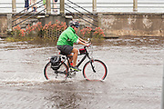 A bicyclist rides through floodwater along the Battery in the historic district as Hurricane Joaquin brings heavy rain, flooding and strong winds as it passes offshore October 4, 2015 in Charleston, South Carolina.