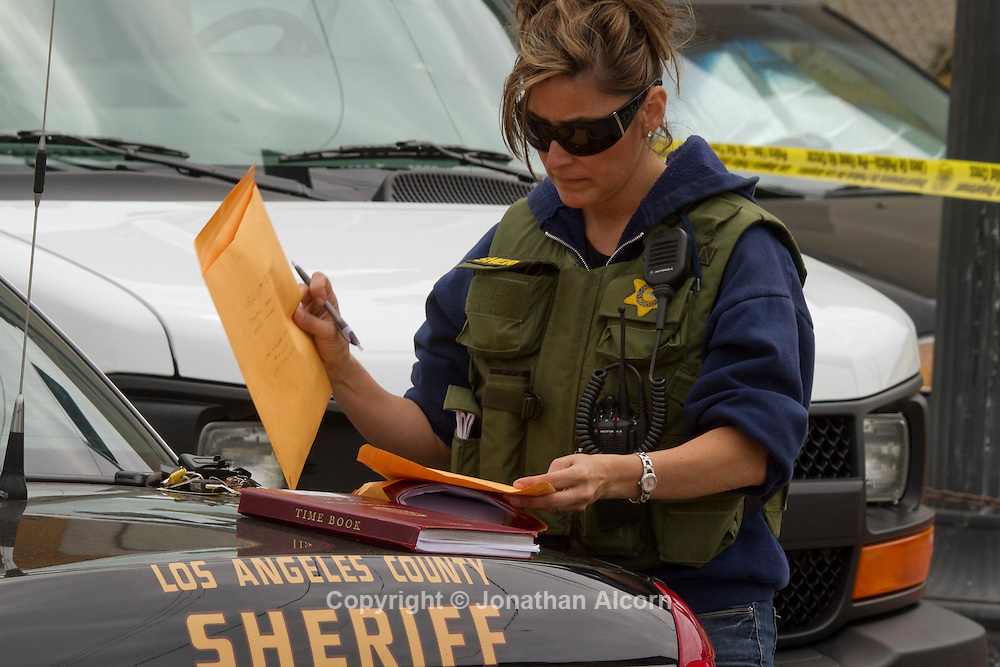 A Los Angeles Sheriff Dept. investigator looks over evidence seized during a search warrant at the Medical Kush Beach Club, a medical marijuana dispensary in the 1300 block of Ocean Front Walk in Venice Beach..© Jonathan Alcorn 2011
