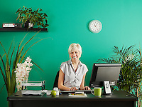 Business woman behind desk in office full of potted plants portrait