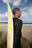 Man holding surfboard standing on beach
