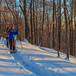 Two women snowshoeing in the forest on Indian Hill in West Newbury, Massachusetts.