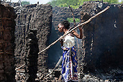 A woman looks trough debry from her burnt house at the village of Kibusu in the Tana Delta of after an attack by alleged Orma raiders.
