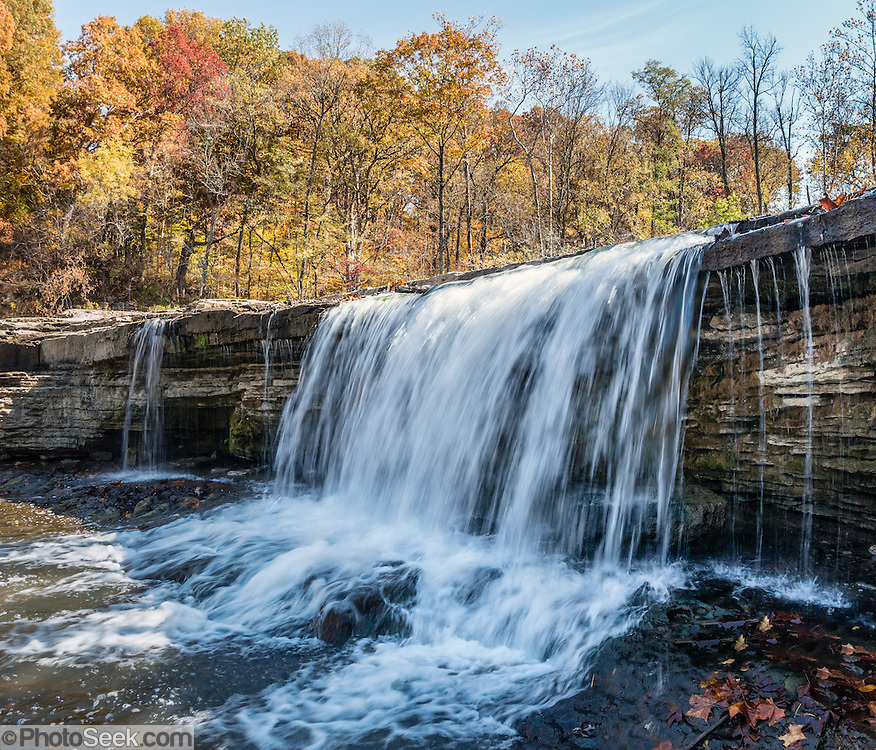 Upper Falls, in Cataract Falls State Recreation Area –  Indiana's largest-volume waterfall. Mill Creek plunges 20 feet in the set of Upper Falls, and a half a mile downstream the Lower Falls drops 18 feet, for a total drop of 86 feet including intermediate cascades. Autumn foliage colors were brilliant but water volume was low for this photo in mid October 2015. The park's limestone outcroppings formed millions of years ago when the region was covered by a large shallow ocean. Cataract Falls State Recreation Area is an hour southwest of Indianapolis, near Cloverdale, Indiana, USA. Vibrant autumn foliage colors glowed for this panorama stitched from 2 overlapping photos captured October 21, 2015.