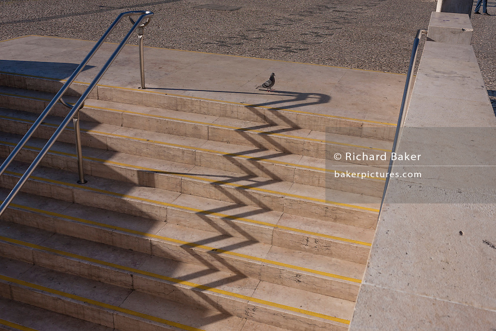 An urban landscape zigzag of shadows from the steps and handrails of Alameda Metro station, on 14th July 2016, in Lisbon, Portugal. One the sunny side are the distorted lines  of the well-trodden stairs at this main transport merge of underground train lines as a lone pigeon walks along the top and person's legs look the same in the far right corner. (Photo by Richard Baker / In Pictures via Getty Images)