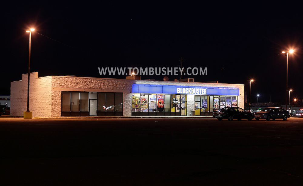 Town of Wallkill, New York - A Blockbuster video rental store, at right, and a vacant store located in the middle of a shopping plaza parking lot at night on Nov. 14, 2010.