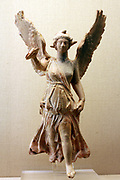 Nike (goddess of Victory) about to land. This terracotta figure of Nike holds out a wreath for a victor, Her garment clings to her body, revealing the contours beneath but also billows out to enhance the sense of rapid movement. Made and found in Myrina, Turkey. About 50BC-AD 30.