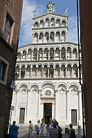 Man in hat photographing San Michele in Foro, a Roman Catholic basilica church in Lucca, Tuscany, central Italy.