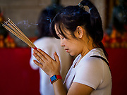 29 JANUARY 2019 - BANGKOK, THAILAND:       A woman prays at Wat Mangon Kamalawat, a large Chinese Buddhist temple in Bangkok's Chinatown district. Chinese New Year celebrations in Bangkok start on February 4, 2019. The coming year will be the Year of the Pig in the Chinese zodiac. About 14% of Thais are of Chinese ancestry and Lunar New Year, also called Chinese New Year or Tet is widely celebrated in Chinese communities in Thailand.   PHOTO BY JACK KURTZ