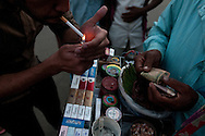 A Bangladeshi man lights a cigarette he purchased from a street vendor who carries a variety of cigarettes for customers on his tray.