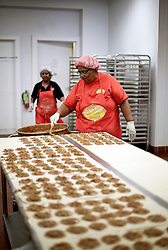 21 September 2015. New Orleans, Louisiana.<br /> Ms Robin McLinton  and Mary Richardson making Aunt Sally's Pralines.<br /> Photo©; Charlie Varley/varleypix.com