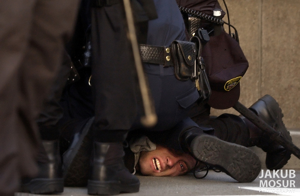 A protester gets pushed to the ground after trying to run away from San Francisco Police after they had rounded up a couple of hundred protesters for walking on Hayes Street during a march in downtown San Francisco on Friday, March 21, 2003. (AP Photo/Jakub Mosur)