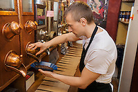Side view of salesperson dispensing coffee beans into bowl at store