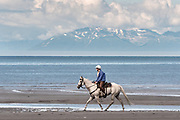 A woman rides her horse along the Cook Inlet past the Chigmit Mountains at Anchor Point, Alaska.