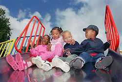 Multiracial group of children at top of slide in playground,