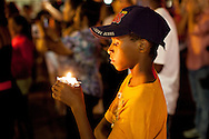 A boy holds a candle during a prayer vigil in front of the Ferguson police station. Protests have been ongoing in Ferguson, Missouri since the shooting death of Michael Brown, the eighteen-year-old unarmed teen killed by police on August 9, 2014.