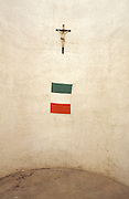 crucifix and Italian flag hanging on a curved wall