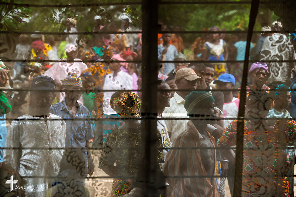 Patients are seen through a window treatment as they wait for the clinic to open on the third day of the LCMS Mercy Medical Team on Wednesday, May 9, 2018, in the Yardu village outside Koidu, Sierra Leone, West Africa. LCMS Communications/Erik M. Lunsford