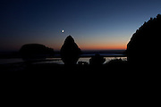 A crescent moon hangs low against the sunset over the rock formations and beach at Samuel H Boardman State Park, Oregon Coast