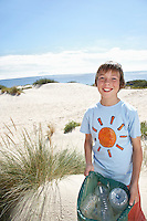Boy (10-12) holding plastic bag on sand dune portrait