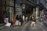 With a further 149 reported dying from Coronavirus in the last 24hrs, taking the UK death toll to 43,320, shoppers observe the 2 metre social distance rule and queue to enter the branch of H&M on Oxford Street, during the Covid pandemic, on 25th June 2020, in London, England.