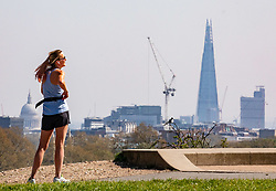 © Licensed to London News Pictures. 15/04/2020. London, UK. A women relaxes in the sun with a view of the Shard while Police patrol Primrose Hill in North London as Ministers decide when and how the lockdown will finish as politicians are warned that the UK could face the worst recession in 300 years. Photo credit: Alex Lentati/LNP