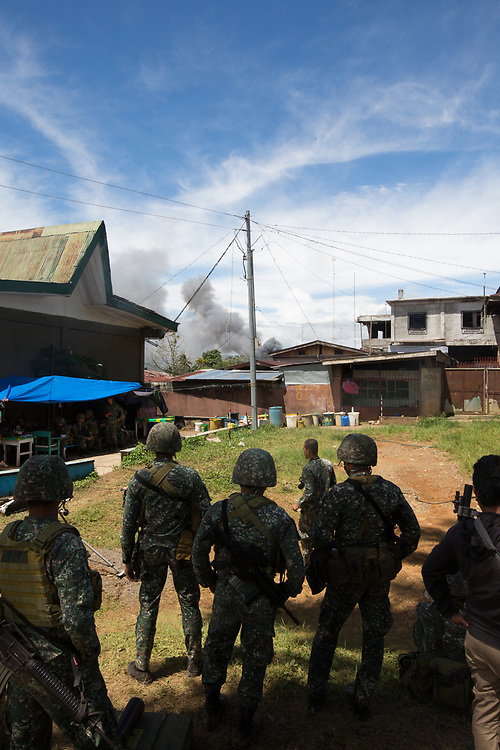 MARAWI, PHILIPPINES - JUNE 9: Philippine marines look at smoke following an airstrikes by Philippine Air Force in Marawi, southern Philippines on June 9, 2017. Philippine military jets fired rockets at militant positions on Friday as soldiers fought to wrest control of the southern city from gunmen linked to the Islamic State group. (Photo: Richard Atrero de Guzman/NUR Photo)