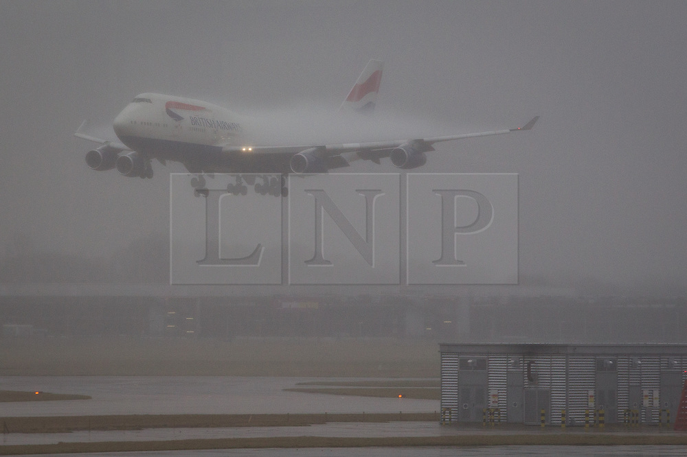 © Licensed to London News Pictures . 22/12/2012 . London , UK . A British Airways aeroplane lands in fog and rain at Heathrow Airport in West London today (22nd December 2012) . Photo credit : Joel Goodman/LNP